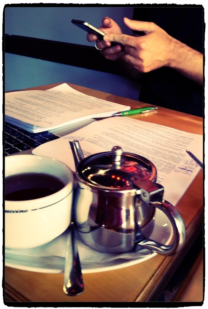 Sur une petite table carrée, on voit un manuscrit annoté, le clavier d'un ordinateur portable, une théière et une tasse de thé pleine.